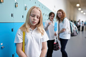 Schoolgirl being bullied in school corridor