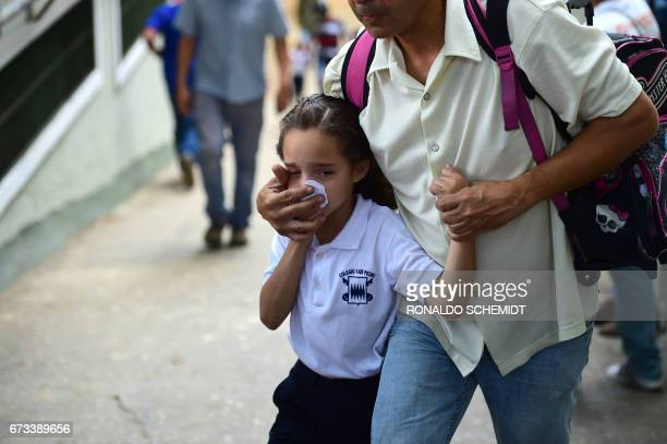 TOPSHOT A schoolgirl covers her nose and mouth to avoid breathing tear gas shot by police at opponents of Venezuelan President Nicolas Maduro...