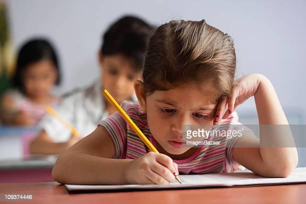 Schoolgirl (4-5) drawing in classroom