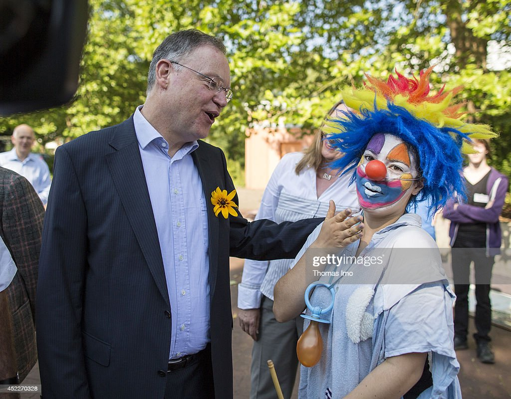 A schoolgirl dressed as a clown recieves Stephan Weil, Prime Minister of German State Lower-Saxony, prior his visit of IGS Georg-Christoph-Lichtenberg Comprehensive School (Gesamtschule) during his summertour through lower saxony on July 17, 2014 in Goettingen, Germany.