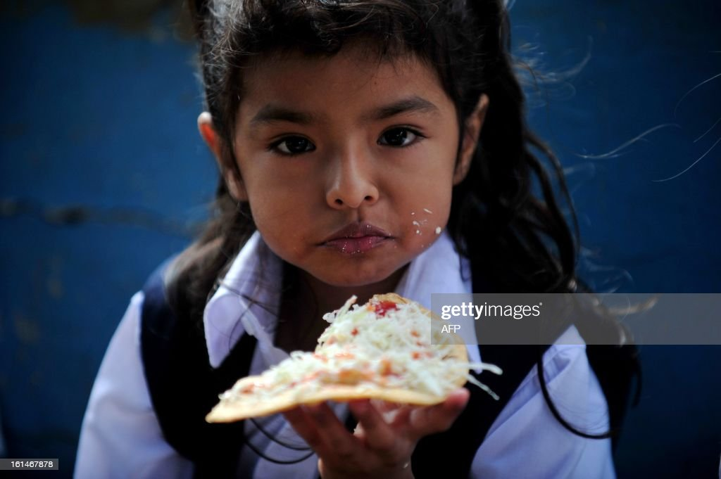 A schoolgirl has a snack in the yard of the Jean Paul Genie primary school during the year's first day of classes, in Managua, on February 11, 2013. AFP PHOTO/Hector RETAMAL