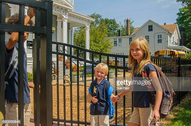 Schoolgirl holding hands with younger brother at school gate