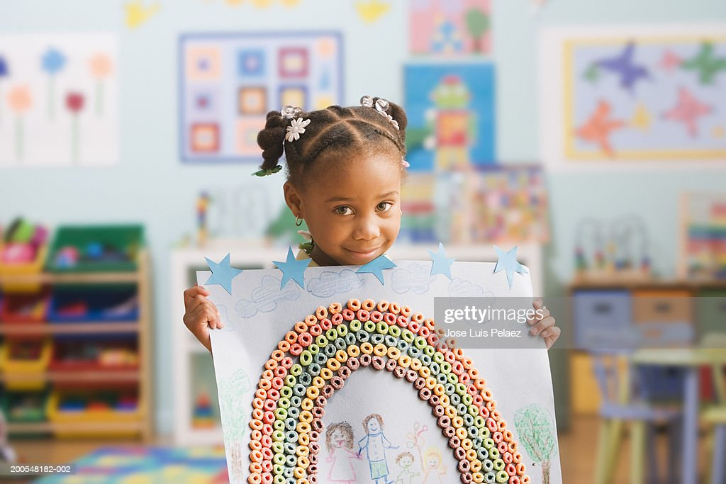 Schoolgirl (4-5) holding up picture, smiling, portrait : Stock Photo