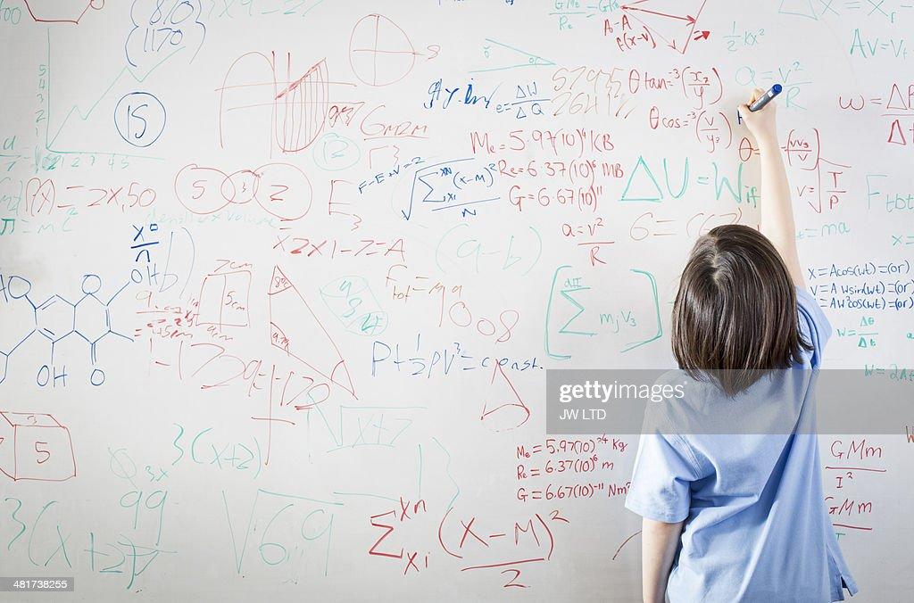 schoolgirl in front of wipe board, math equations : Stock Photo