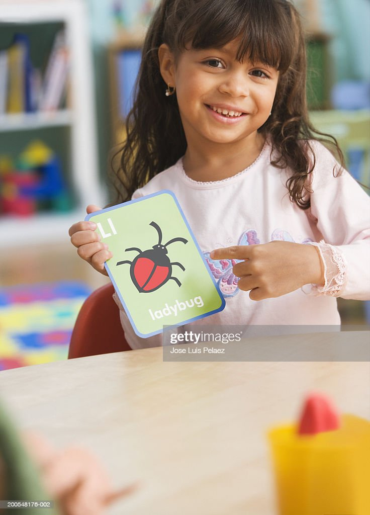 Schoolgirl l(4-5) holding ladybug card, smiling, portrait : Stock Photo