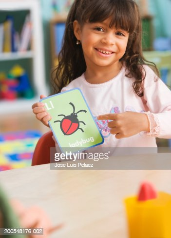 Schoolgirl l(4-5) holding ladybug card, smiling, portrait : Stock Photo