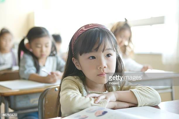 Schoolgirl listening lecture in classroom