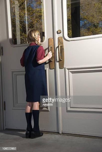 Schoolgirl looking through window in a large door