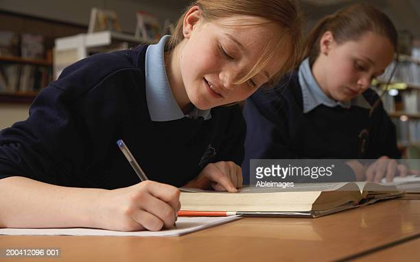 Schoolgirl (11-13) making notes from book in library, smiling
