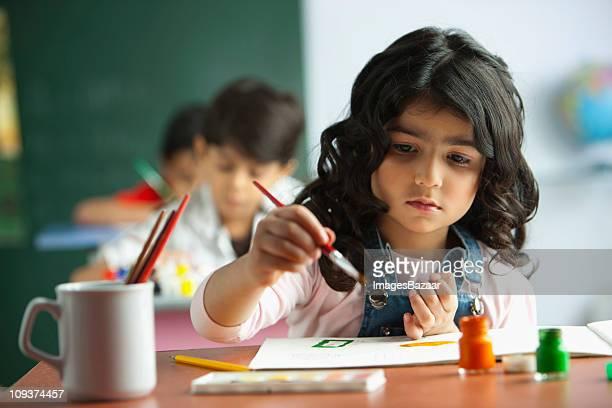 Schoolgirl (4-5) painting in classroom