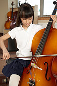 Schoolgirl (6-12) playing cello in music room, smiling