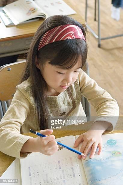 Schoolgirl (6-7) playing pencil at desk