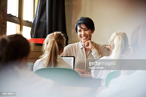 Schoolgirl reading on tablet for teacher in class