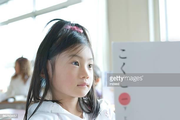Schoolgirl (8-9) reading textbook in classroom