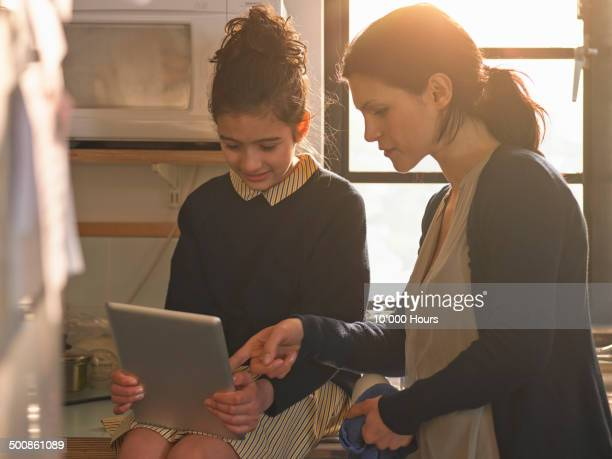 Schoolgirl showing her mother home work on an ipad