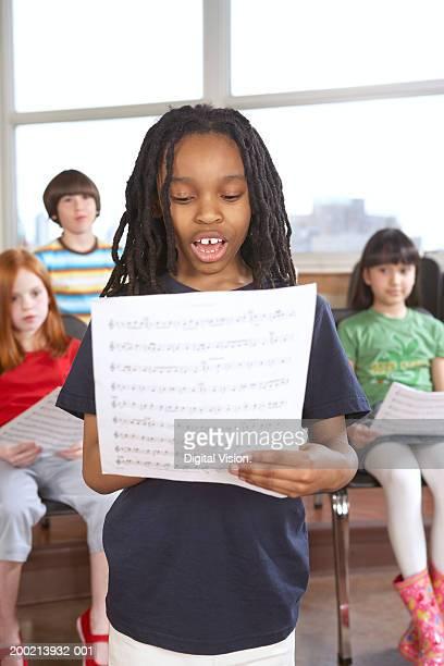Schoolgirl (6-12) singing from music sheet in classroom