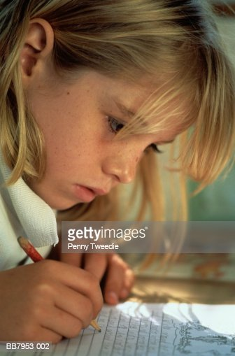 Schoolgirl (8-10) sitting at desk, writing, close-up : Stock Photo