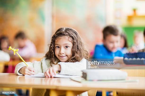 Schulkind-Nur Mädchen Sitzen im Klassenzimmer und Blick in die Kamera.