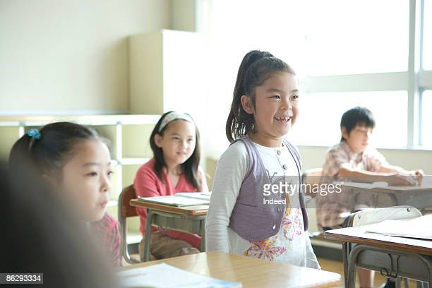 Schoolgirl (8-9) standing and answering in class