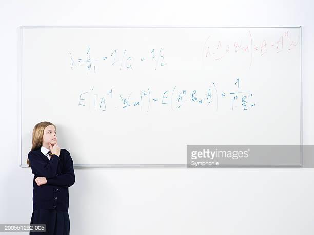 Schoolgirl (12-13) standing by whiteboard, looking up