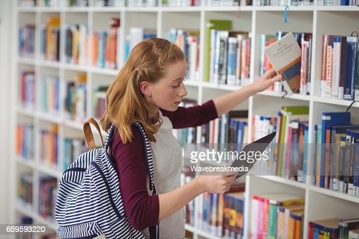 Schoolgirl using digital tablet while selecting book in library : Stock Photo