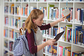 Schoolgirl using digital tablet while selecting book in library at school