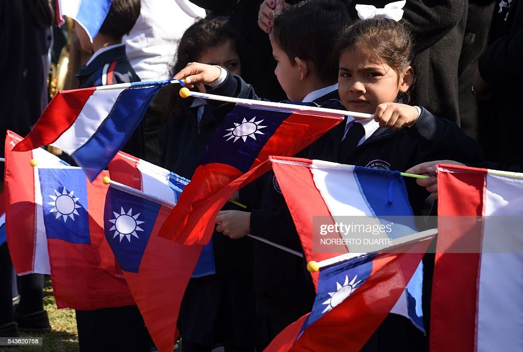 A schoolgirl waves flags of Taiwan and Paraguay during the visit of Taiwan's President Tsai Ing-wen to the General Andres Rodriguez school to which the country donated computers, in Asuncion on June 29, 2016. Taiwan's new president is visiting Paraguay as part of her first overseas trip since taking office in May. / AFP / NORBERTO