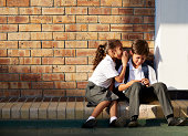 Schoolgirl whispering in classmates ear, outside