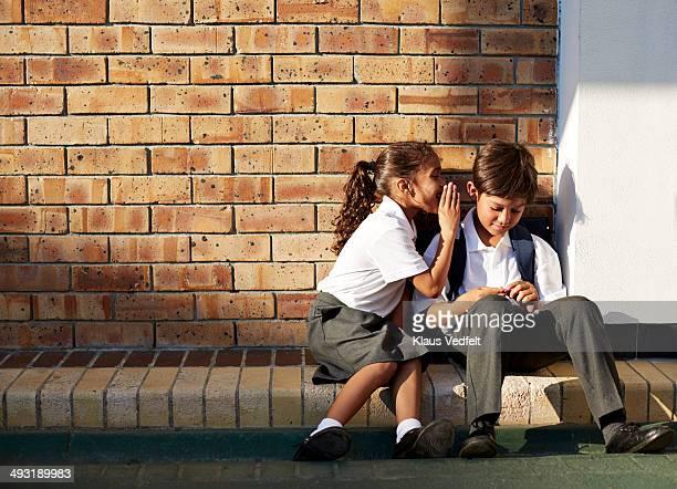 Schoolgirl whispering in classmates ear, outside