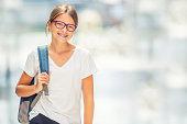 Schoolgirl with bag, backpack. Portrait of modern happy teen school girl with bag backpack. Girl with dental braces and glasses.