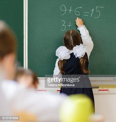 Schoolgirl writing at blackboard