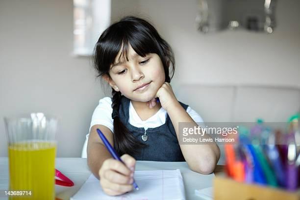 Niña en edad escolar escrito en escritorio