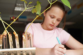 Schoolgirl (11-13) writing notes, plants in test tubes in foreground