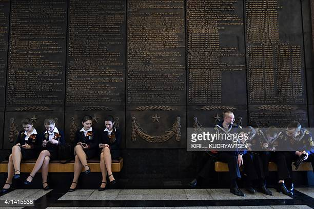 Schoolgirls and navy cadets rest on banquettes at the Museum of the Great Patriotic War at Poklonnaya Gora in Moscow on April 28 2015 Russia...