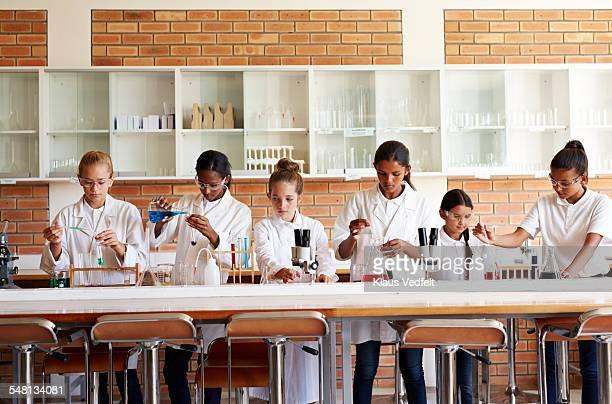 Schoolgirls doing science experiments with liquids