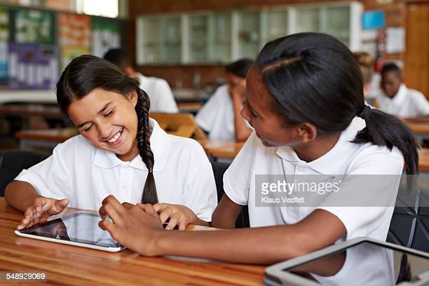 Schoolgirls exploring tablet together in class