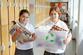 Schoolgirls holding a collection of recycling