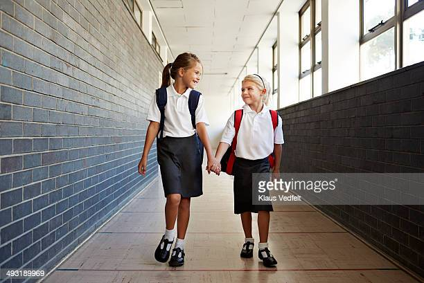Schoolgirls holding hands in the corridor