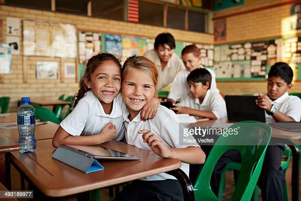 Schoolgirls hugging in classroom