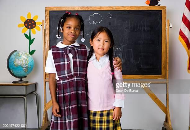 Schoolgirls (4-7) hugging, portrait
