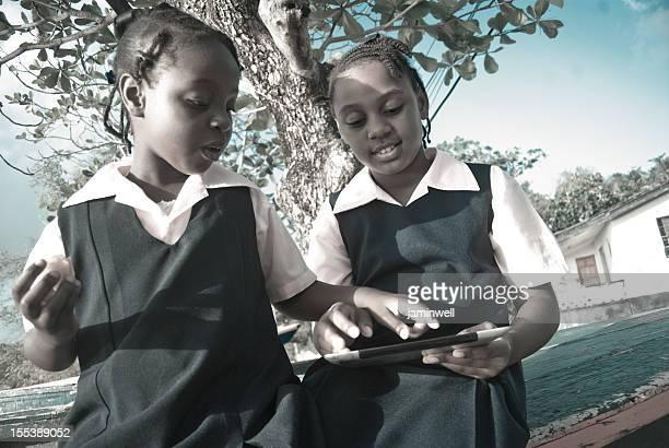 schoolgirls in uniform on digital tablet outdoors