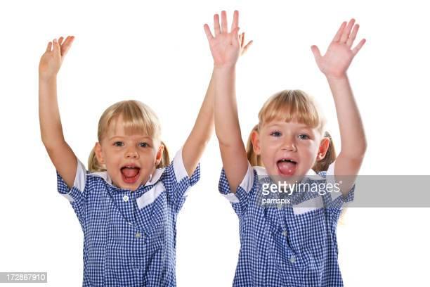 Schoolgirls in uniforme con braccia sollevate