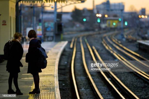Schoolgirls look down the track to see any approaching tube trains at Turnham Green station in West London 05 February 2001 The Underground network...