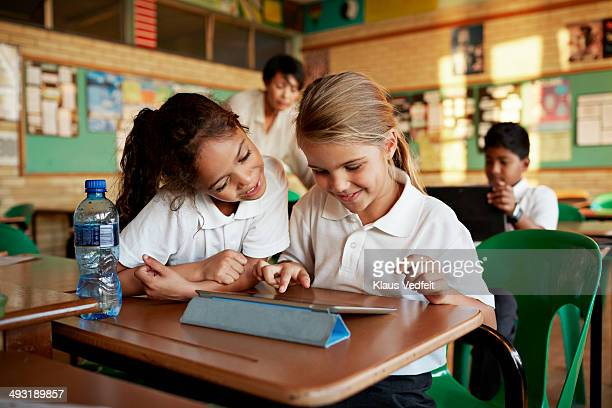 Schoolgirls looking at tablet togther and smiling