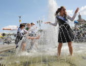 Schoolgirls play in fountains during a gathering of school graduates on Independence Square in Kiev on May 30 2008 Young Ukrainians on Friday mark '...