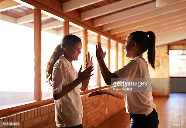 Schoolgirls playing clapping game in school isle