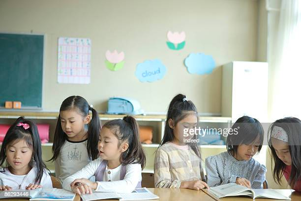 Schoolgirls (6-9) reading textbook in classroom