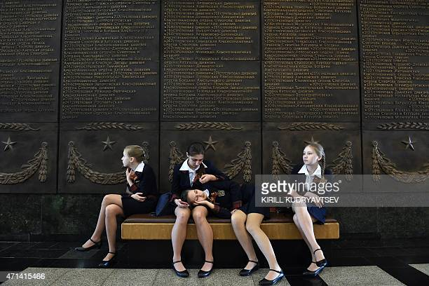 Schoolgirls rest on a banquette at the Museum of the Great Patriotic War at Poklonnaya Gora in Moscow on April 28 2015 Russia celebrates the 70th...