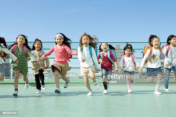 Schoolgirls (6-9) running