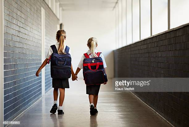 Schoolgirls walking hand in hand at school isle